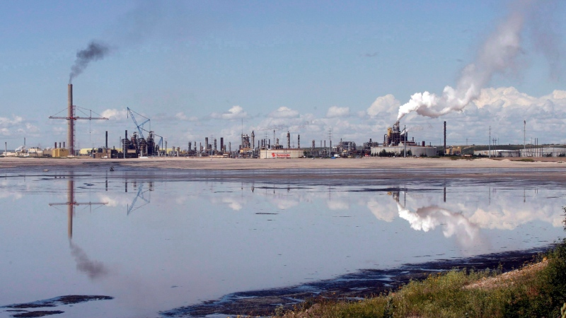 A tailings pond reflects the Syncrude oilsands mine facility near Fort McMurray, Alta., Wednesday, July 9, 2008. (THE CANADIAN PRESS/Jeff McIntosh)