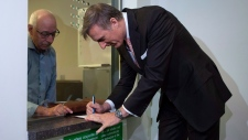 Maxime Bernier signs papers as he files the papers