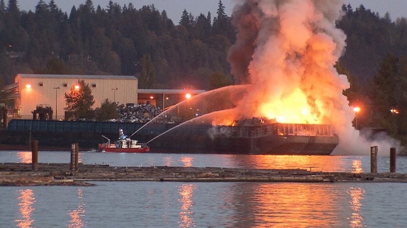 A fire boat works to extinguish a barge fire in Surrey, B.C. on Tuesday, Oct. 9, 2018.