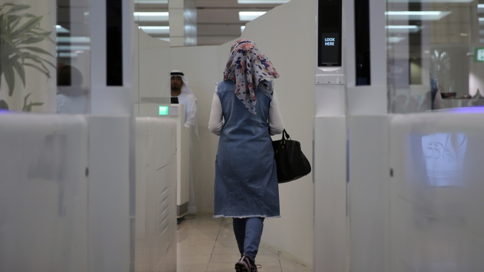 "A passenger walks through the Smart Tunnel at the airport in Dubai, United Arab Emirates, Wednesday, Oct. 10, 2018. Passport control looked a little different today in Dubai at the world's busiest airport for international travel, after it debuted a new ""smart tunnel."" (AP Photo/Kamran Jebreili)"