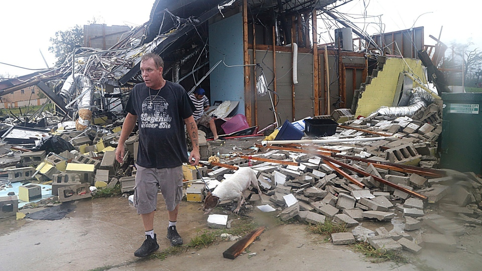 Brian Bon inspects damages in the Panama City downtown area after Hurricane Michael made landfall in Panama City, Fla., Wednesday, Oct. 10, 2018. (Pedro Portal/Miami Herald via AP)