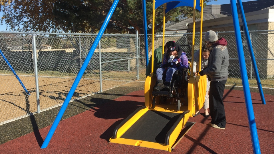 Natasha Esau rides the wheelchair accessible swing at Saskatoon's first sensory playground at John Dolan School. (Laura Woodward/CTV Saskatoon)