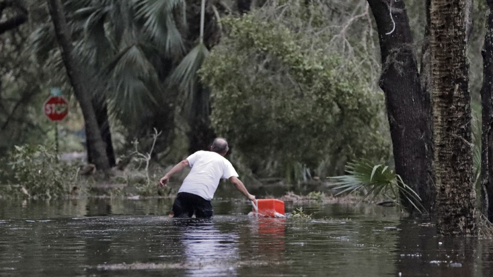 A resident of St. Marks, Fla., rescues a cooler out of the floodwaters near his home Wednesday, Oct. 10, 2018. (Chris O'Meara / AP)