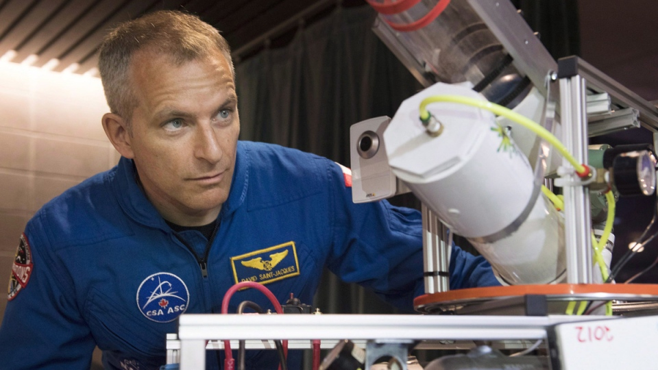 Astronaut David Saint-Jacques looks at a model robot at the FIRST Quebec robotics competition in Montreal, on March 3, 2018. (Graham Hughes / THE CANADIAN PRESS)