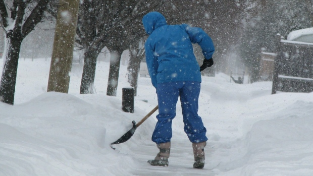 A person shoveling snow from a sidewalk