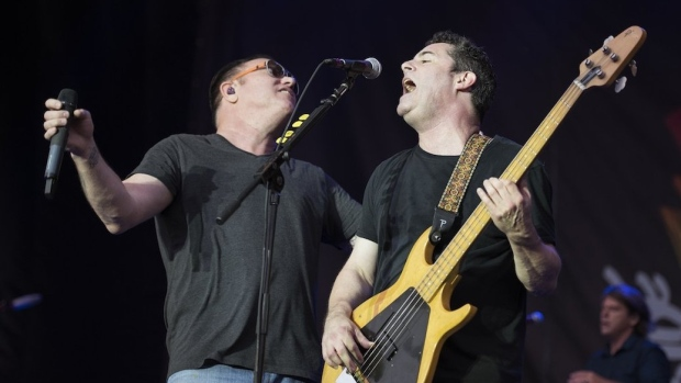 Two members of Smashmouth sharing the stage
