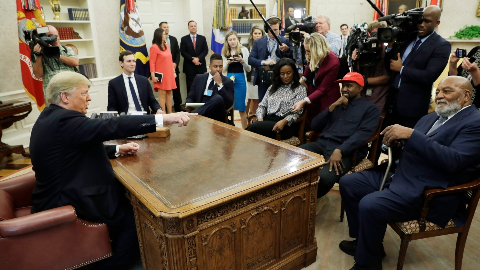 U.S. President Donald Trump talks to NFL Hall of Fame football player Jim Brown, seated right, and rapper Kanye West, seated center, and others in the Oval Office of the White House, Thursday, Oct. 11, 2018, in Washington. (AP Photo/Evan Vucci)