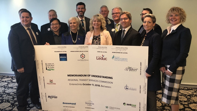 Leaders from the 13 communities in the Edmonton Metropolitan Region pose with the Memorandum of Understanding for a Regional Transit Services Commission they signed on Thursday, October 11, 2018. (Twitter/Edm Mayor Office)
