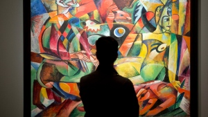 "A patron looks at Heinrich Campendonk's ""Harlequin and Columbine"" at the ""From Van Gogh to Kandinsky: Impressionism to Expressionism"" exhibit at the Museum of Fine Arts in Montreal on Tuesday, Oct. 7, 2014. (THE CANADIAN PRESS/Ryan Remiorz)"