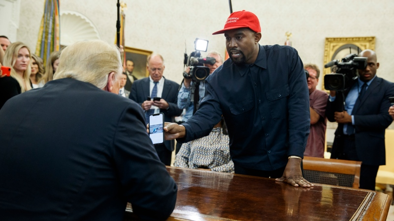 Rapper Kanye West shows President Donald Trump a photograph of a hydrogen plane during a meeting in the Oval Office of the White House, Thursday, Oct. 11, 2018, in Washington. (AP Photo/Evan Vucci)