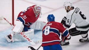 Montreal Canadiens goaltender Carey Price makes a save against Los Angeles Kings' Jake Muzzin (6) as Canadiens' Jordie Benn defends during secnond period NHl hockey action in Montreal, Thursday, October 11, 2018. THE CANADIAN PRESS/Graham Hughes