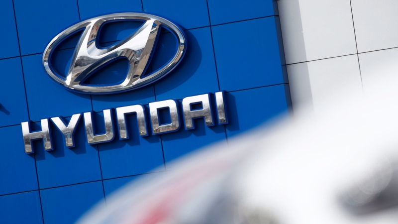 In this April 15, 2018, file photo the company logo hangs on the side of a showroom as a long row of unsold 2018 Sonatas sits on a Hyundai dealer's lot in the south Denver suburb of Littleton, Colo. (AP Photo/David Zalubowski)