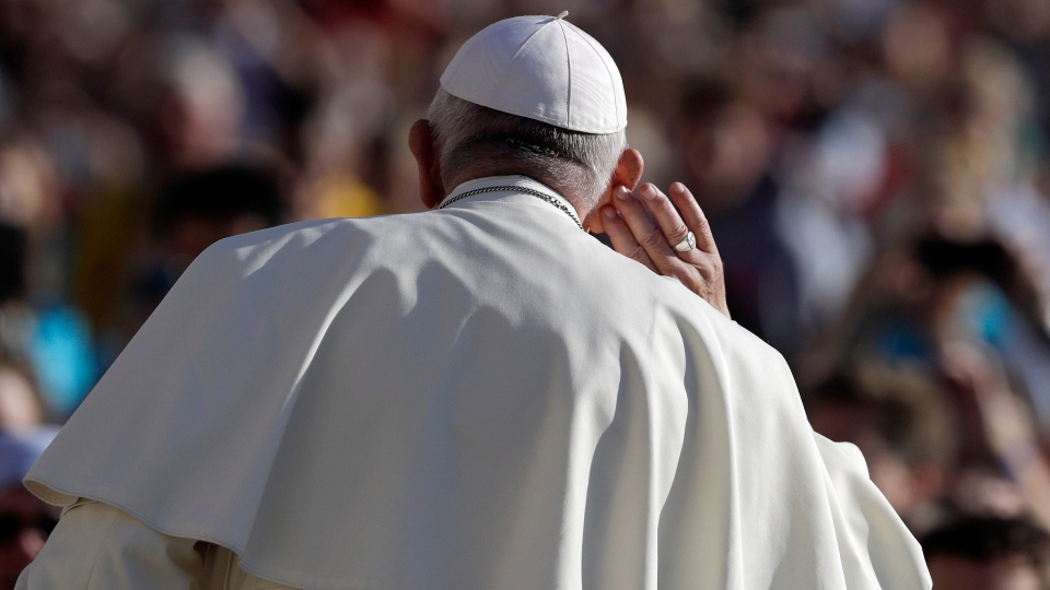 Pope Francis touches his ear as he arrives with the popemobile in St.Peter's Square on the occasion of his weekly general audience at the Vatican, Wednesday, Oct. 10, 2018. (AP Photo/Gregorio Borgia)