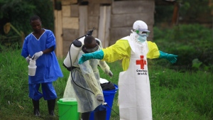 In this Sept. 9, 2018, file photo, a health worker sprays disinfectant on his colleague after working at an Ebola treatment center in Beni, Eastern Congo. Sometimes violent community resistance is complicating efforts to contain Congo's latest Ebola outbreak, causing the rate of new cases to rise. (AP Photo/Al-hadji Kudra Maliro, File)