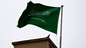 A bird sits by a Saudi Arabia's flag on the roof top of Saudi Arabia's consulate in Istanbul, Sunday, Oct. 14, 2018. (AP Photo/Petros Giannakouris)