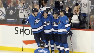 Winnipeg Jets' Josh Morrissey (44), Patrik Laine (29), Nikolaj Ehlers (27), Bryan Little (18) and Jacob Trouba (8) celebrate after Little scored against the Carolina Hurricanes during third period NHL hockey action in Winnipeg, Sunday, October 14, 2018. THE CANADIAN PRESS/Trevor Hagan