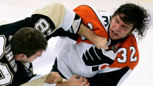 In this Tuesday, Oct. 14, 2008, file photo, Pittsburgh Penguins' Eric Godard, left, and Philadelphia Flyers' Riley Cote (32) fight in the first period of an NHL hockey game in Pittsburgh. As Cote took and delivered countless punches over more than a decade of junior and pro hockey, he was eager to avoid painkillers. Now a handful of years into retirement, Cote is a proponent of cannabis and its oils as an alternative to more addictive drugs commonly used by athletes to play through pain. (AP Photo/Gene J. Puskar, File
