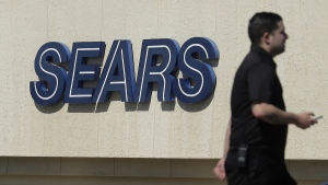 A man walks in front of a Sears sign in San Bruno, Calif., on March 28, 2018. (Jeff Chiu / AP)