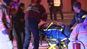 Emergency crews treat a man who was trapped in a car that flipped over