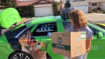 Customer Maureen Blaskovich grabs a coconut water from the backseat window of a self-driving car, a Lincoln MKZ outfitted with technology by AutoX, in San Jose, Calif. on Aug. 29, 2018. Internal government documents show that more than one million jobs could be lost to automated vehicles, with ripple effects far beyond the likeliest professions. A presentation federal officials put together last year predicts automation could kill some 500,000 transportation jobs, from truck drivers to subway operators to taxi drivers and even courier services, but doesn't put a timeline to the potential losses. (THE CANADIAN PRESS/AP, Ryan Nakashima)