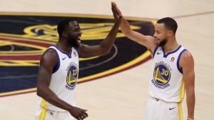 Golden State Warriors' Draymond Green, left, and Stephen Curry celebrate during the first half against the Cleveland Cavaliers in Game 3 of basketball's NBA Finals, Wednesday, June 6, 2018, in Cleveland. (AP Photo/Carlos Osorio)