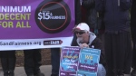 Man with posters about bill 148 minimum wage