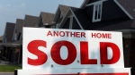 A for sale sign displays a sold home in a development in Ottawa on July 6, 2015. (THE CANADIAN PRESS / Sean Kilpatrick)