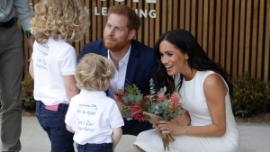 Prince Harry and Meghan, Duchess of Sussex, receive native flowers from Finley Blue and Dasha Gallagher, left, at Taronga Zoo in Sydney, Australia, Tuesday, Oct. 16, 2018. (AP Photo/Kirsty Wigglesworth,Pool)