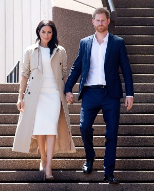 Prince Harry and Meghan, Duchess of Sussex walk down steps outside the Opera House to meet members of the public during a walk about in Sydney, Australia, Tuesday, Oct. 16, 2018. (Paul Edwards/Pool via AP)