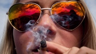 A woman smokes a joint during the annual 4-20 cannabis culture celebration at Sunset Beach in Vancouver, B.C., on Thursday, April 20, 2017. THE CANADIAN PRESS/Darryl Dyck