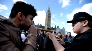 A man shares a his marijuana joint during the annual 4/20 marijuana celebration on Parliament Hill in Ottawa on Friday, April 20, 2018. (Justin Tang/ The Canadian Press)