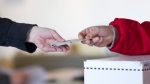An election official hands back to a voter her marked ballot to place in a ballot box. (The Canadian Press/Chris Young)