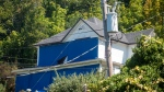 "FILE -- In this file photo taken Aug. 17, 2015, the home featured in the 1985 classic ""The Goonies"" is covered in blue tarps to deter fans from getting too close to the house, in Astoria, Ore. (Joshua Bessex /Daily Astorian via AP, file)"