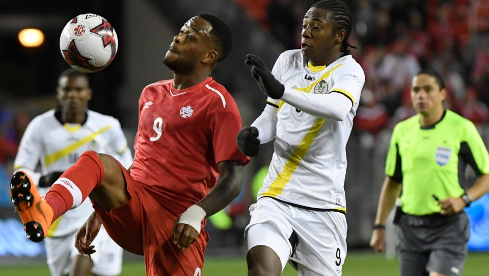 Canada's Cyle Larin, left, and Dominica's Javid George (9) battle for control of the ball during second half Concacaf Nations League qualifier soccer action in Toronto on Tuesday, October 16, 2018. THE CANADIAN PRESS/Nathan Denette