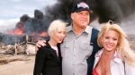 "In this March 25, 2007, file photo, Moonlite Bunnyranch brothel owner Dennis Hof poses with two of his ""working girls"" Brooke Taylor, left, and a woman working under the name ""Airforce Amy"", right, as firefighters burn down remains of the former Mustang Ranch 2 brothel east of Reno, Nev. (AP Photo/Debra Reid)"