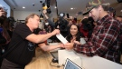 Canopy Growth CEO Bruce Linton, left to right, provides the receipt for the first legal cannabis for recreation use sold in Canada to Nikki Rose and Ian Power at the Tweed shop on Water Street in St. John's N.L. at 12:01 am NDT on Wednesday October 17, 2018. THE CANADIAN PRESS/Paul Daly
