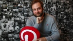 In this Thursday, Oct. 11, 2018, photo Evan Sharp, Pinterest co-founder and chief product officer, poses for a photo in his office beside a wall of pinned photos he has taken at Pinterest headquarters in San Francisco. (AP Photo/Ben Margot)