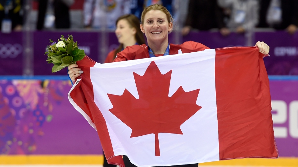 In this Feb. 21, 2014, file photo, Canada's Hayley Wickenheiser celebrates with the Canadian flag after beating the USA 3-2 in overtime at the Sochi Winter Olympics in Sochi, Russia. (AP Photo/Paul Chiasson, The Canadian Press, File)