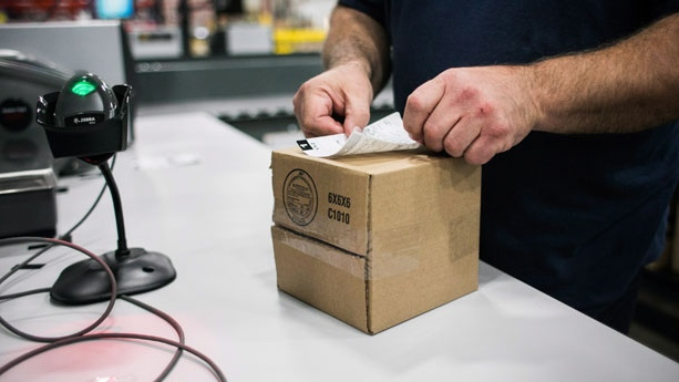 A worker applies a shipping label to a package of cannabis products at the Ontario Cannabis Store distribution centre in an undated handout photo. THE CANADIAN PRESS/HO-Ontario Cannabis Store