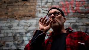 "Jimson Bienenstock smokes a joint during a ""Wake and Bake"" legalized marijuana event in Toronto on Wednesday, October 17, 2018. (THE CANADIAN PRESS / Christopher Katsarov)"