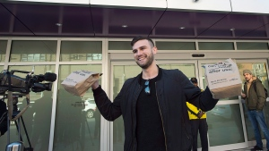 Isaac Langille displays his purchases as he leaves the Nova Scotia Liquor Corporation cannabis store in Halifax on Oct. 17, 2018. (THE CANADIAN PRESS/Andrew Vaughan)