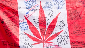 People hold up a Canadian flag with a marijuana logo on it outside a government cannabis store in Montreal, Wednesday, Oct. 17, 2018. THE CANADIAN PRESS/Graham Hughes
