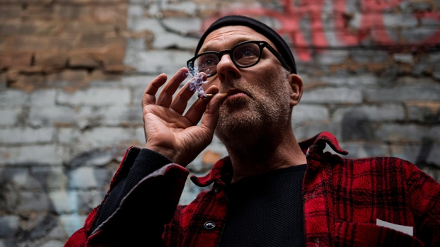 "Jimson Bienenstock smokes a joint during a ""Wake and Bake"" legalized marijuana event in Toronto on Wednesday, Oct. 17, 2018. THE CANADIAN PRESS/Christopher Katsarov"