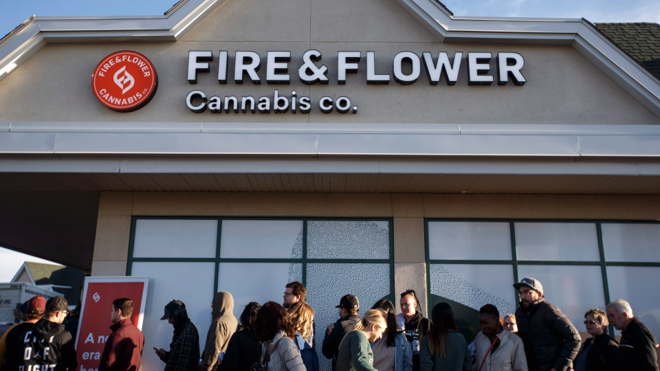 Customers wait in line for the opening of Fire and Flower, where they can purchase legal marijuana, in Edmonton, Alta., on October 17, 2018. THE CANADIAN PRESS/Jason Franson