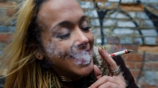 "Krissy Calkins smokes a marijuana joint at a ""Wake and Bake"" legalized marijuana event in Toronto on Wednesday, October 17, 2018. THE CANADIAN PRESS/Christopher Katsarov"