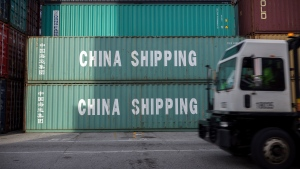 FILE- In this July 5, 2018, file photo, a jockey truck passes a stack of 40-foot China Shipping containers at the Port of Savannah in Savannah, Ga. (AP Photo/Stephen B. Morton, File)