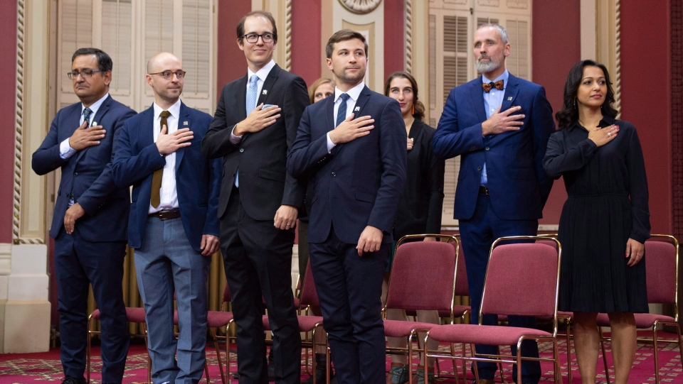 Quebec Solidaire MNAs put their hands to their heart as they pledge allegiance to Quebec, after they were sworn in as member of the National Assembly Wednesday, October 17, 2018 at the legislature in Quebec City. (THE CANADIAN PRESS/Jacques Boissinot)