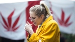 A woman smokes cannabis in a Toronto park on Wednesday, October 17, 2018, as they mark the first day legalization of Cannabis across Canada. (THE CANADIAN PRESS/Chris Young)