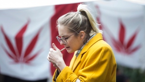 A woman smokes cannabis in a Toronto park on Wednesday, October 17, 2018, as they mark the first day legalization of cannabis across Canada. THE CANADIAN PRESS/Chris Young