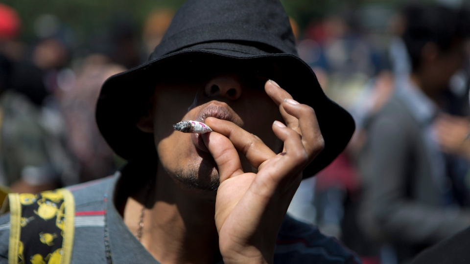 A young man smokes marijuana during a celebration marking Cannabis International Day in Mexico City, Friday, April 20, 2018. (AP Photo/Eduardo Verdugo)